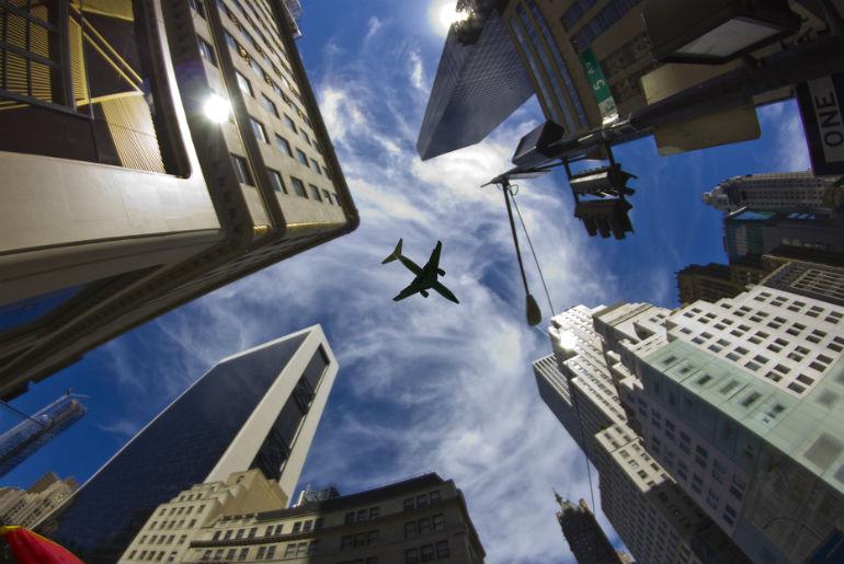 jet plane flying over skyscrapers New York City