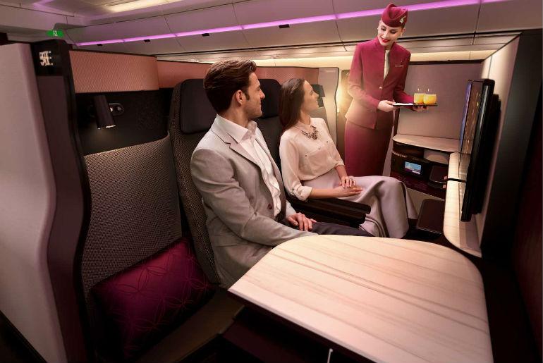 Couple sitting in the Qatar airways Qsuite