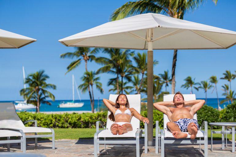 Couple relaxing sun tan at luxury beach hotel resort