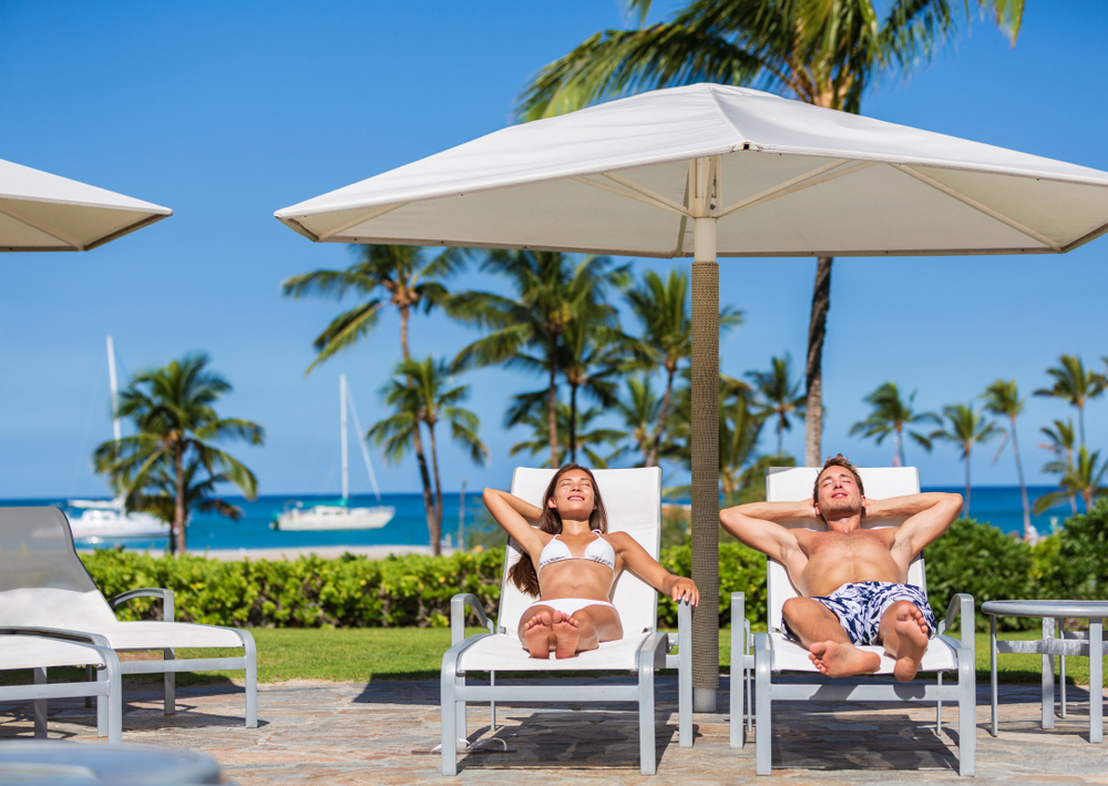 Couple relaxing sun tan at luxury beach hotel resort