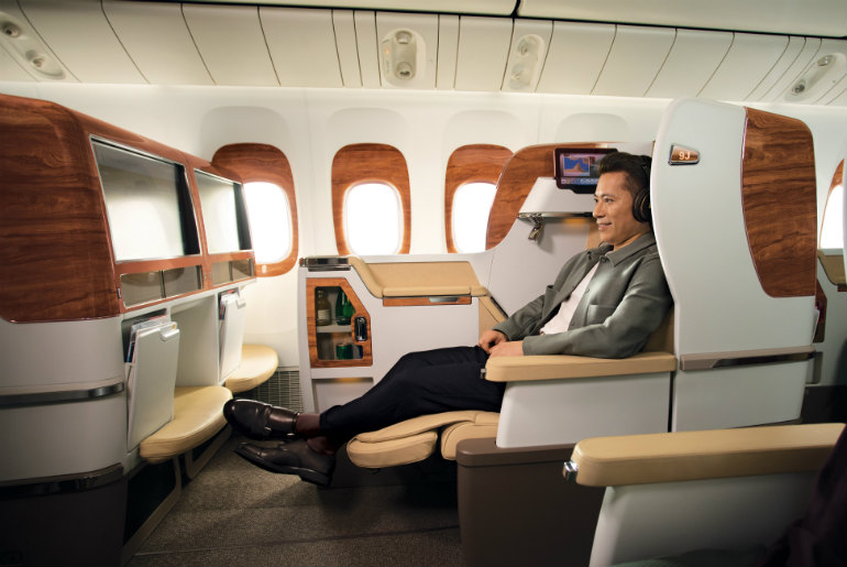 A man stretching out on Emirates Business Class cabin