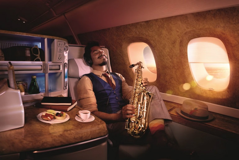 a man relaxing in Emirates business class
