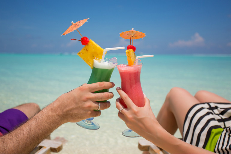 Hands with colourful cocktails on the beach
