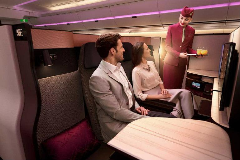 A couple sitting in Qatar Airways Qsuite cabin