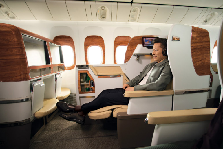 A man in a Emirates business class cabin