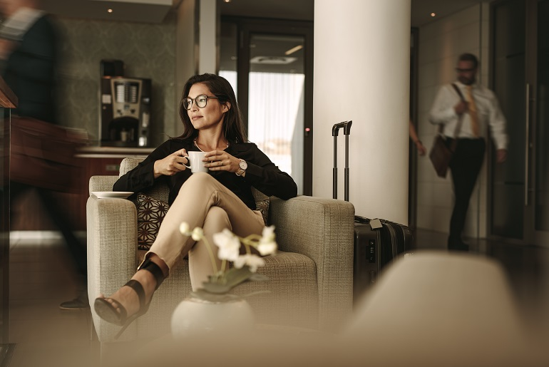 Business woman enjoying cup or tea in a business class airport lounge